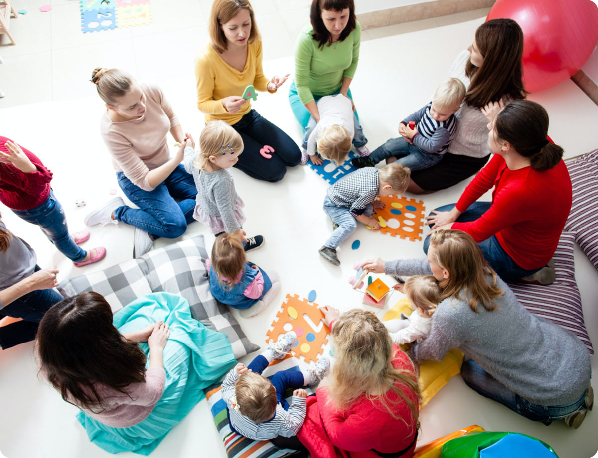 an image of a group of mothers sitting in a circle with their baby listening to a woman who is showing them all something