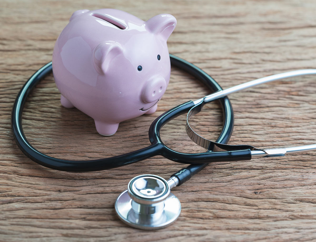 a piggy bank on a desk with a stethoscope wrapped around it