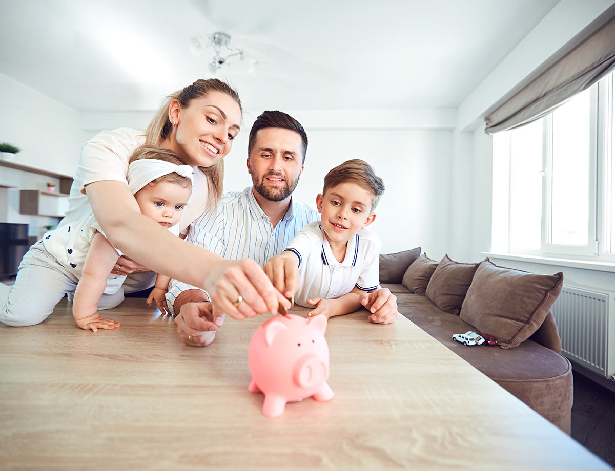 a family of four putting coins into a piggy bank in their kitchen