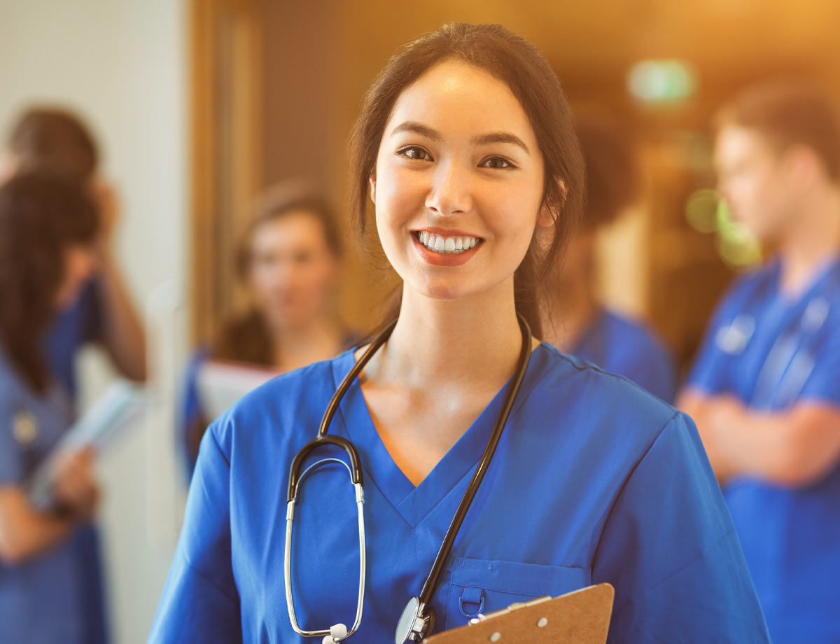 an image of a young female health care professional in blue scrubs smiling with people blurry in the background behind her