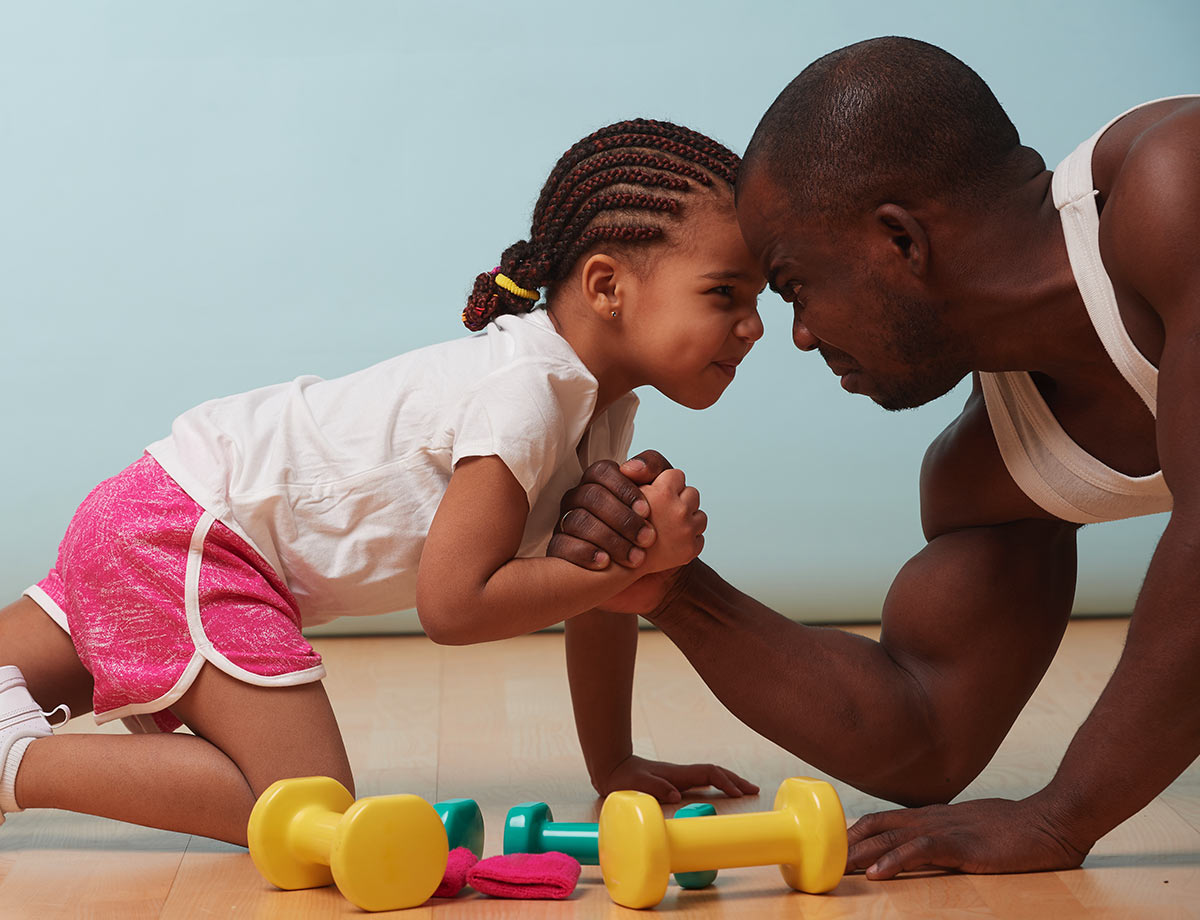 a little girl and her dad playfully arm wrestling on the floor with small fitness weights in front of them